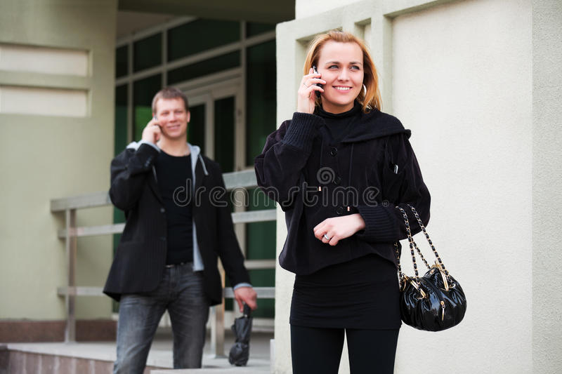 Young man and woman calling on the cell phone stock photo