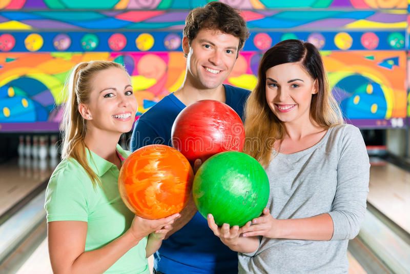 Young people playing bowling and having fun royalty free stock image