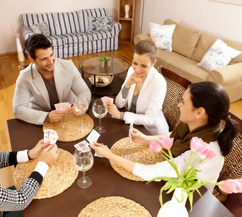 Young people playing cards at home. Having fun stock images