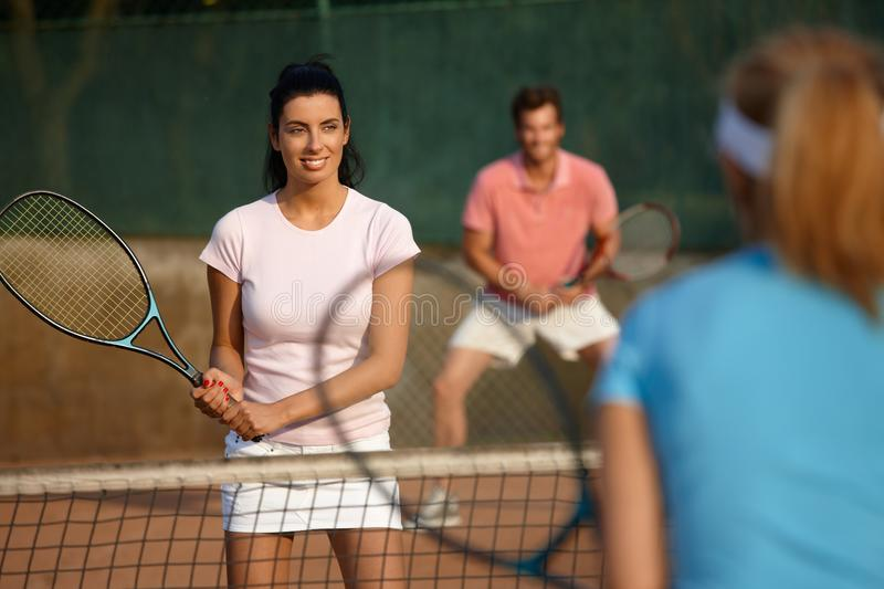 Young people playing mixed doubles. Young people playing tennis, mixed doubles, smiling stock photography