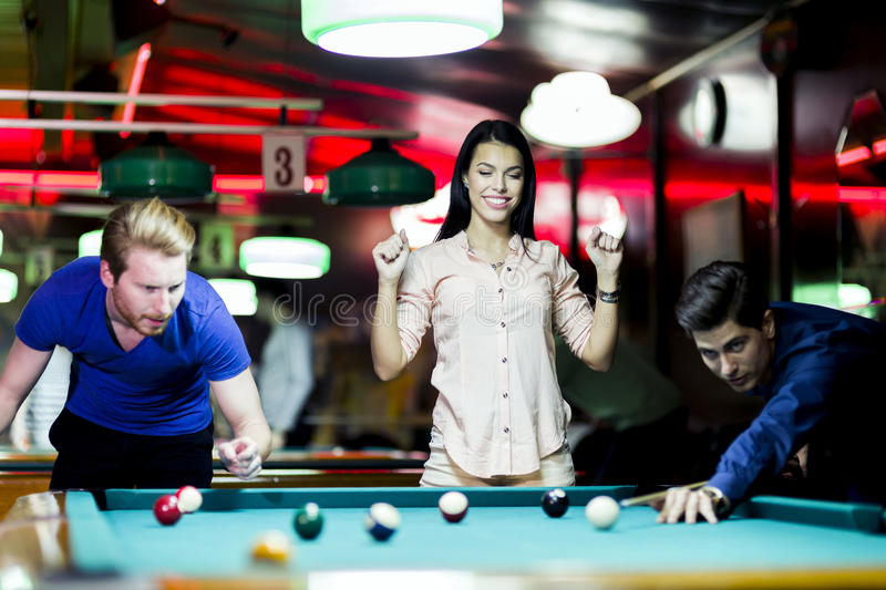 Young people playing snooker in a club pub bar. Young people playing billiard in a club pub bar stock photos