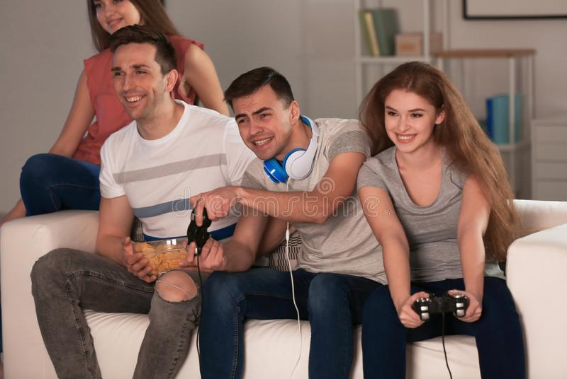 Young people playing video games at home in evening stock photography