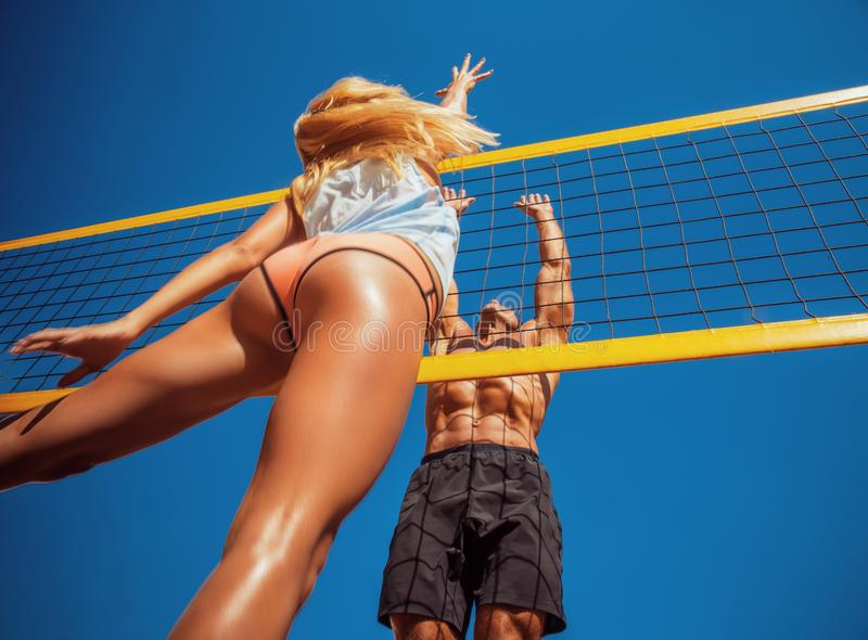 Young people playing volleyball on the beach. royalty free stock image