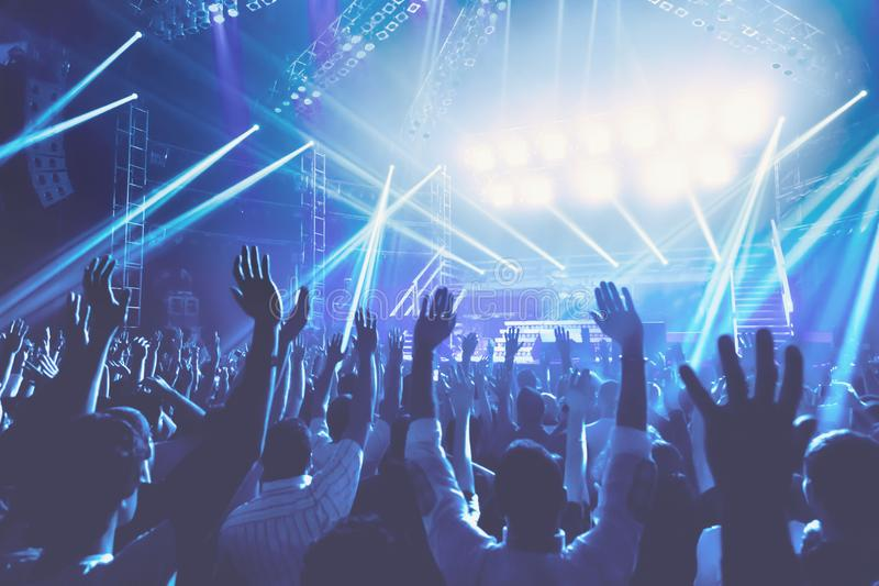 Concert. Young people with pleasure spending evening on the concert, crowd with raised up hands standing in blue lights, singing and enjoying music concept royalty free stock photography
