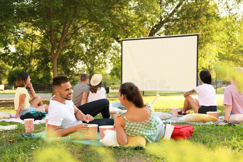 Young people with popcorn watching movie in open air cinema royalty free stock photos