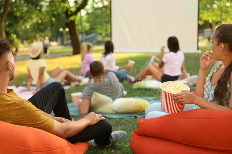 Young people with popcorn watching movie in open air cinema stock photos