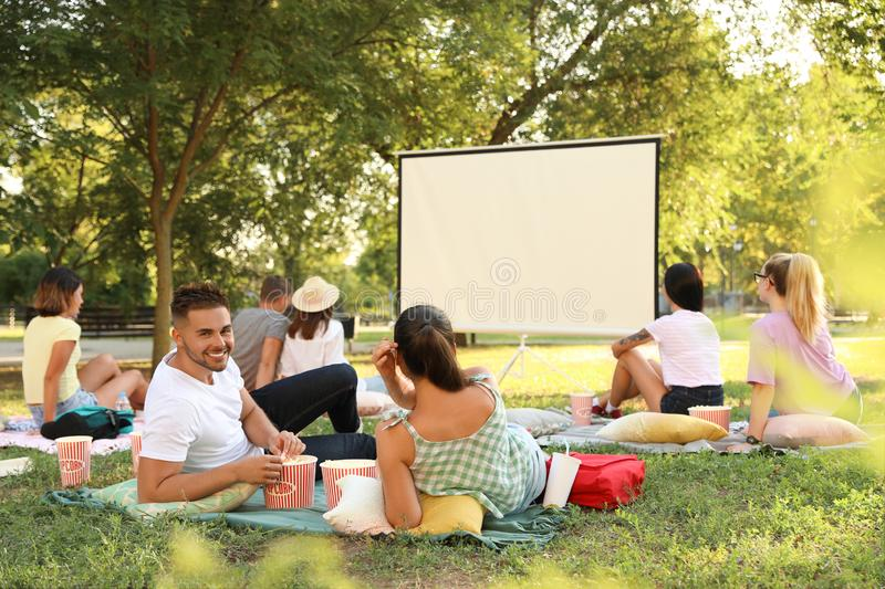 Young people with popcorn watching movie in open air cinema stock images