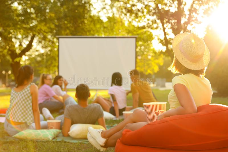 Young people with popcorn watching movie in open air cinema stock image