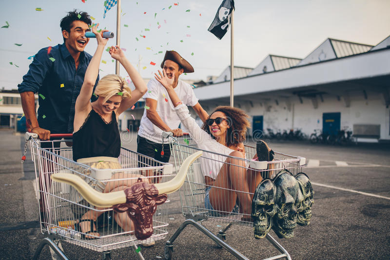 Young people racing with shopping cart and celebrating with conf stock image
