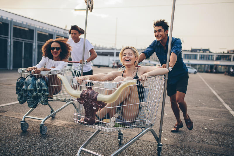 Young people racing with shopping trolleys. On road. Multiracial group of friends racing with shopping cart royalty free stock images