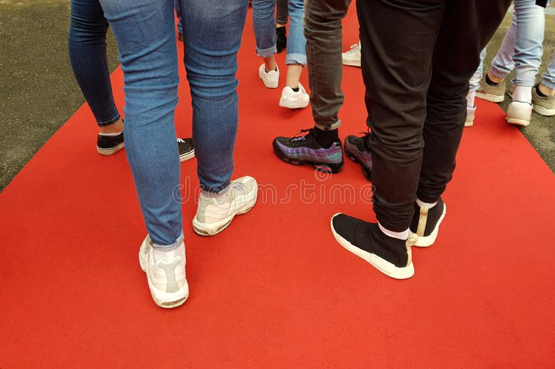 Young people on the red carpet. Legs in sports shoes royalty free stock image
