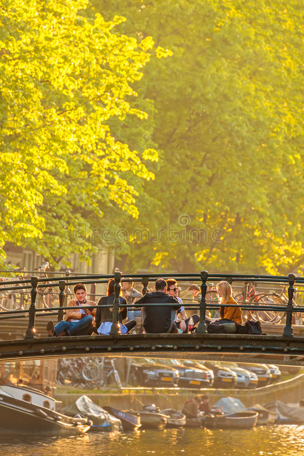 Young people relaxing on an Amsterdam canal bridge during sunset royalty free stock photos