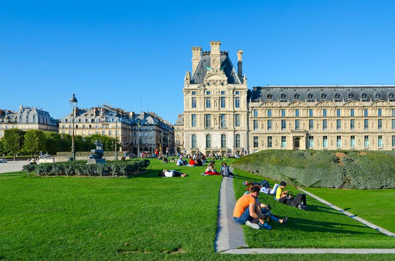 Young people are relaxing on green lawn in park, Paris, France royalty free stock photo