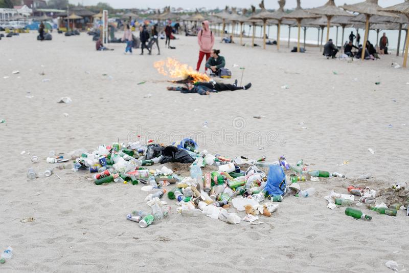 Young people rest on the beach amongst debris especially empty bottles royalty free stock photos