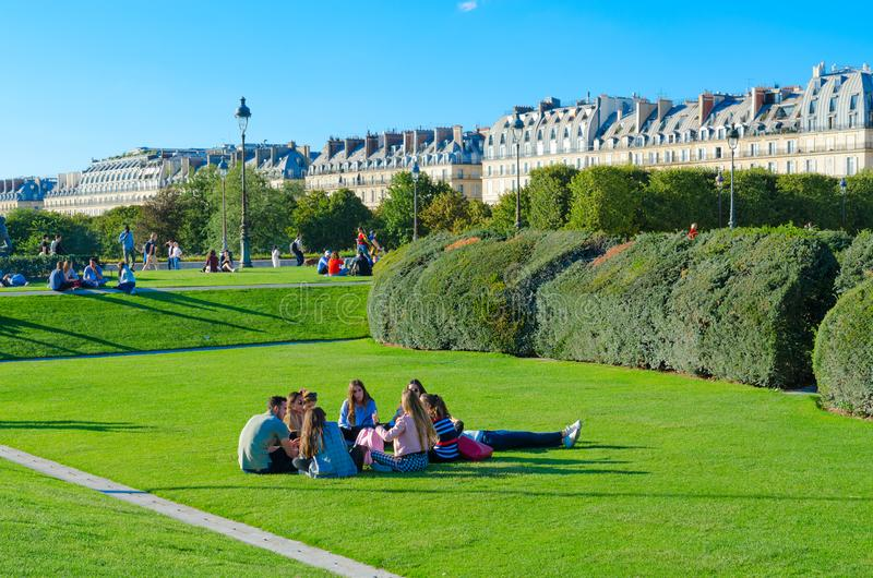 Young people rest on green lawn in park near architectural ensemble of Louvre, Paris, France stock photo