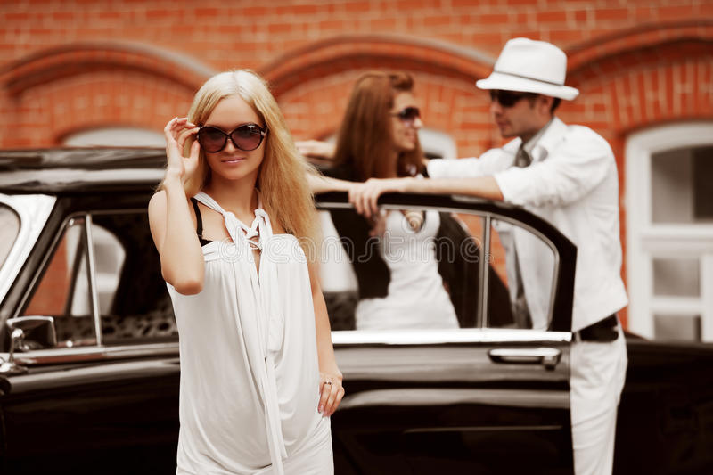 Young fashion people at the retro car stock photo