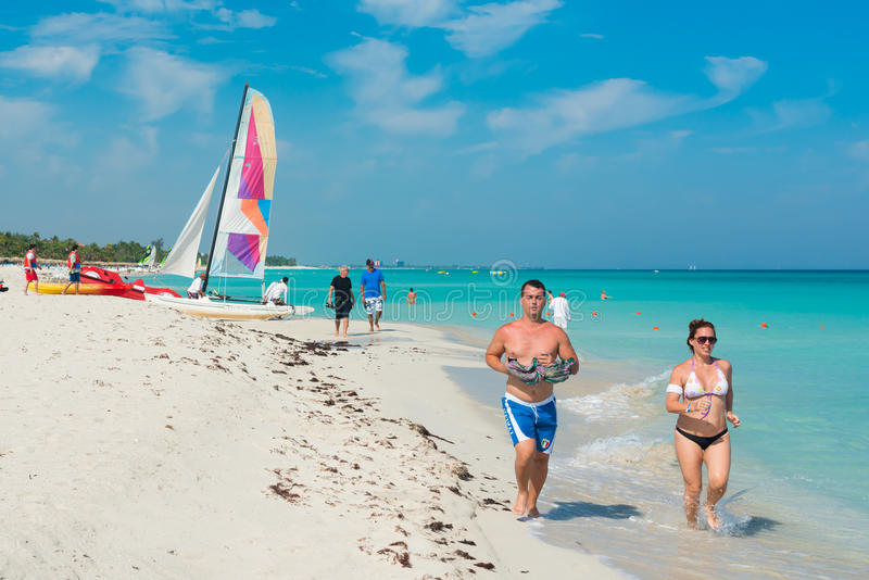 Young people running along the beach in Varadero,Cuba royalty free stock photo
