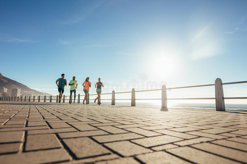 Young people running on ocean water front stock photos