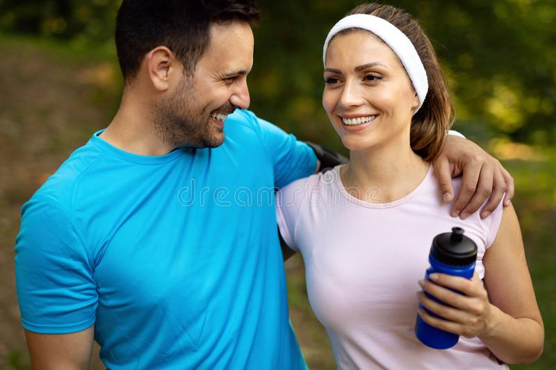 Young people running outdoors. Couple or friends of runners exercising in park. Young people running outdoors. Couple or friends of runners exercising in nature stock image