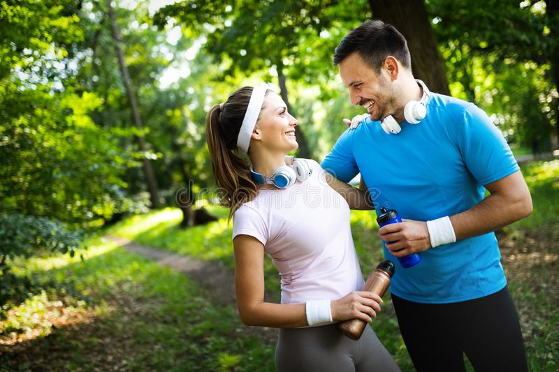 Young people running outdoors. Couple or friends of runners exercising in park. Young people running outdoors. Couple or friends of runners exercising in nature royalty free stock images