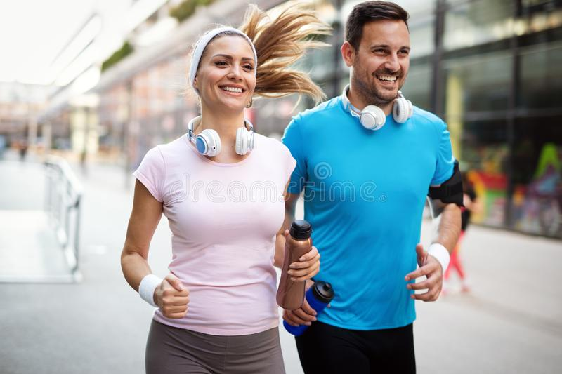 Young people running outdoors. Couple or friends of runners exercising. Together stock photography
