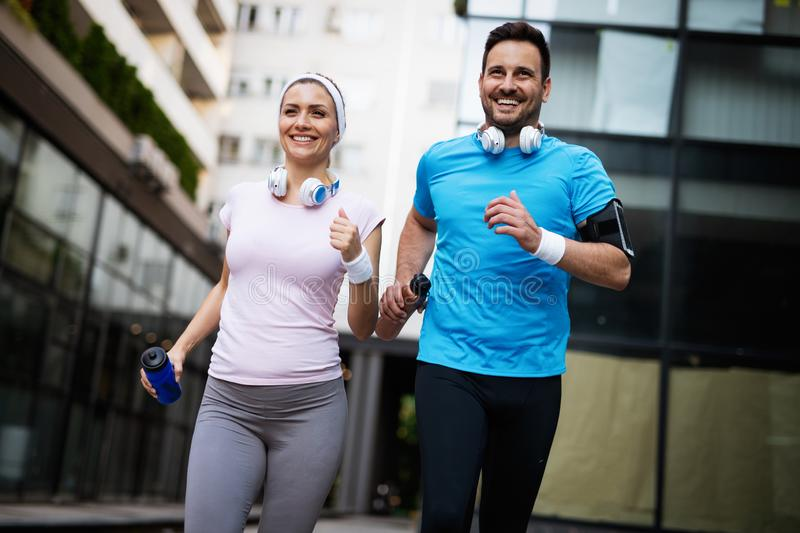 Young people running outdoors. Couple or friends of runners exercising. Together royalty free stock photo