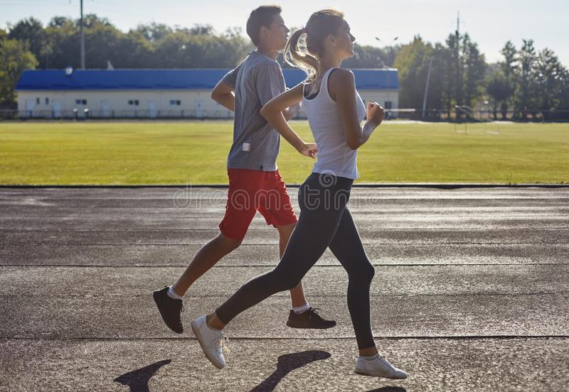 Young people running outdoors. Couple of runners on morning run. Young people running outdoors on a stadium. Couple of runners on morning run royalty free stock photos