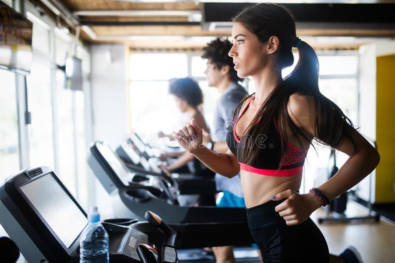 Young people running on a treadmill in health club. royalty free stock photos