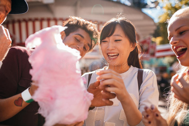 Young people sharing cotton candy outdoors stock photography