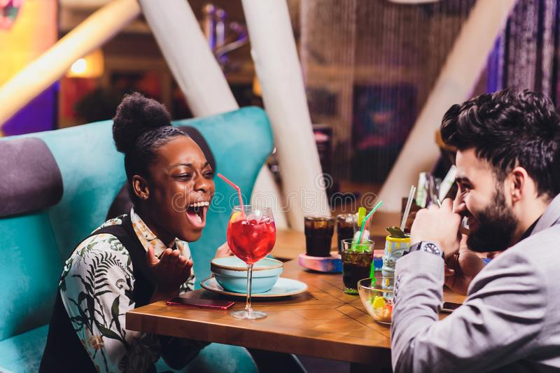 Young people sitting in a cafe and talking. Young man and woman meeting at cafe table. stock photos
