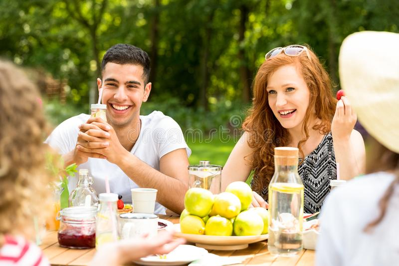 Young people sitting in the garden, drinking water, eating fruit. And laughing stock images