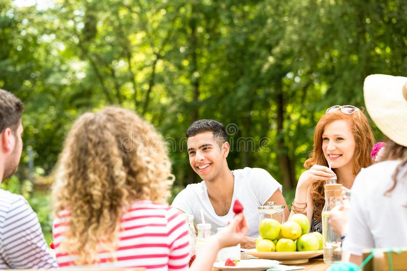 Young people sitting in the garden and spending time together. Concept photo stock image