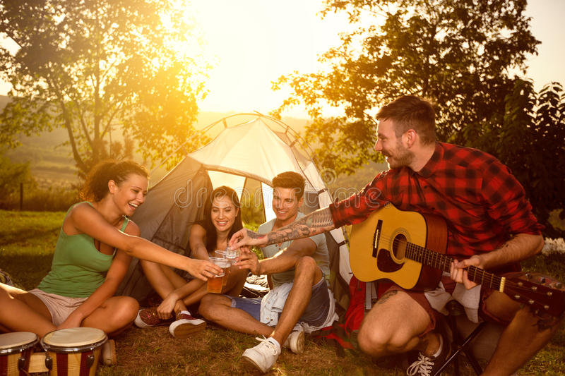 Young people sitting next tent and toasting with beer. Group of young people sitting next tent and toasting with beer, friends on vacation stock image