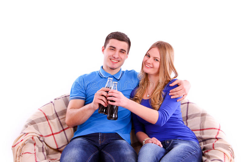 Young people sitting on a sofa and drinking soda royalty free stock photos