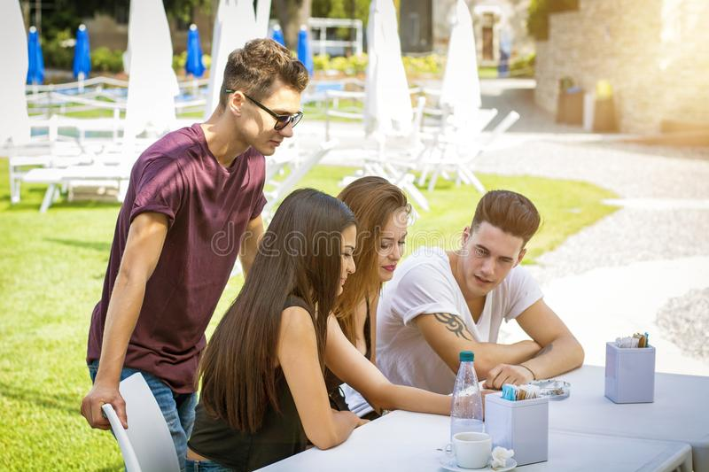 Young people sitting at table having fun stock image