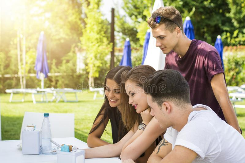 Young people sitting at table having fun royalty free stock photo