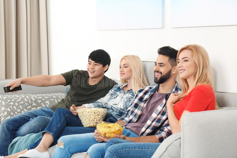 Young people with snacks watching TV on sofa. At home royalty free stock photo