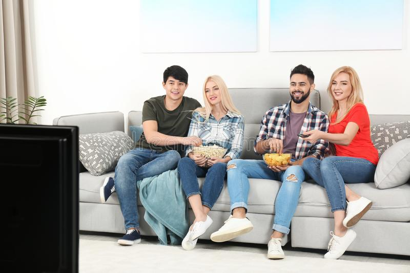 Young people with snacks watching TV on sofa. At home royalty free stock photos