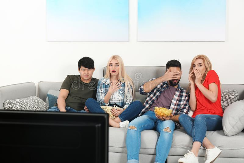 Young people with snacks watching TV on sofa. At home royalty free stock photography