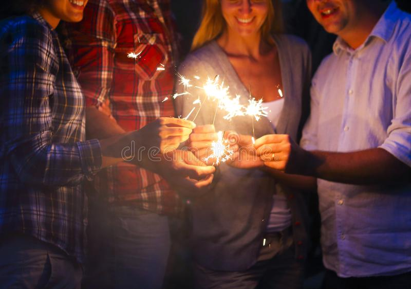 Young people with sparklers having fun on outdoor party royalty free stock photography