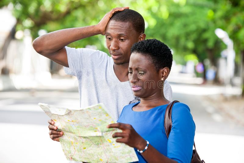 Portrait of young people. Young people standing in the street looking at geographical map with strange air royalty free stock photography