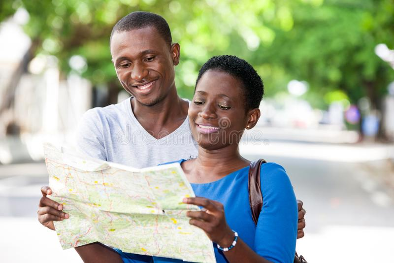 Portrait of young people. Young people standing in the street looking at map geographical smiling stock photos