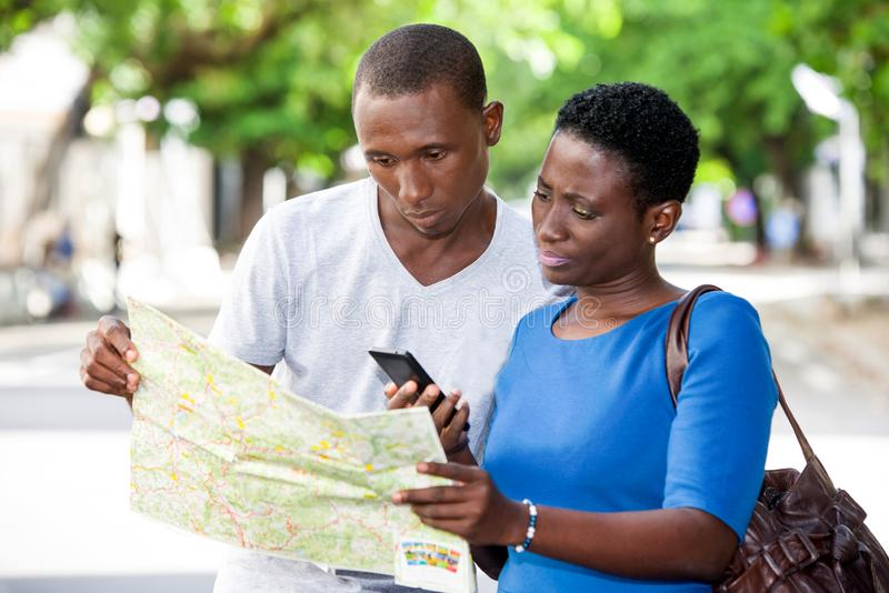 Portrait of young people. Young people standing in the street looking at map stock image
