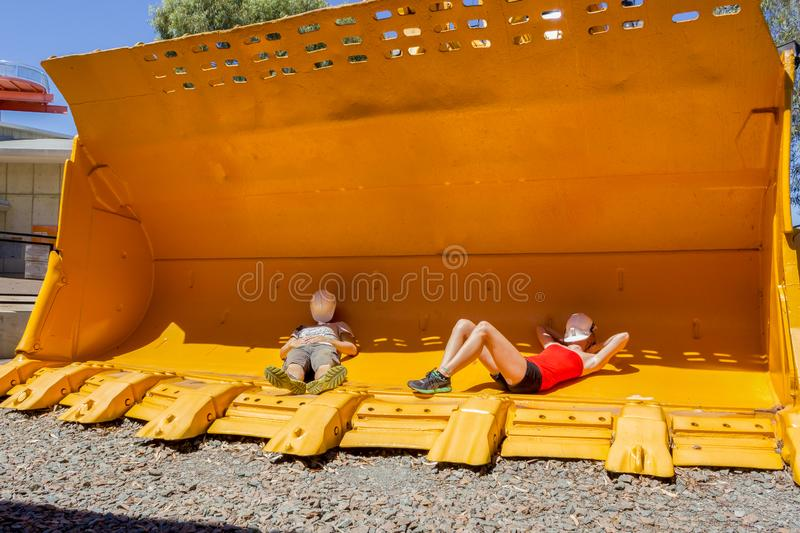 2 young people taking a nap in a mining front loader bucket for scale. Australia stock photos