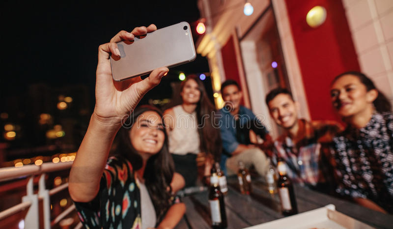 Young people taking self portrait during party stock photography