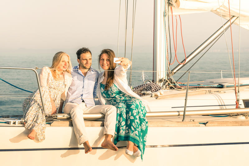 Young people taking selfie on exclusive luxury sailing boat. Concept of friendship and travel with best friends using modern smartphone as new trends and royalty free stock photos