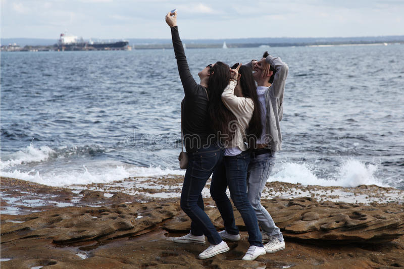 Young people taking a selfie. Group of three young people gathering to take a selfie photo and posing cutely stock image