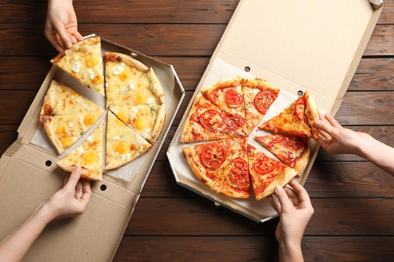 Young people taking slices of hot cheese pizzas from cardboard boxes at table, top view. Food delivery service royalty free stock images