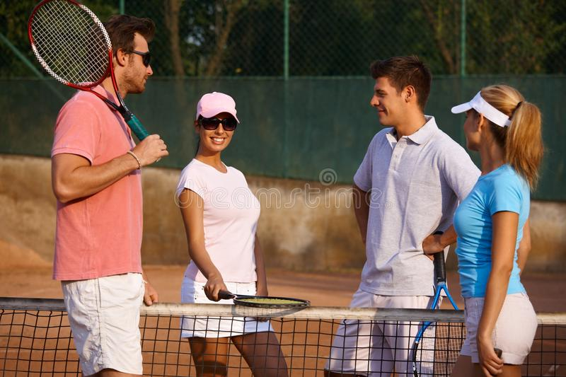 Young people on tennis court smiling stock images
