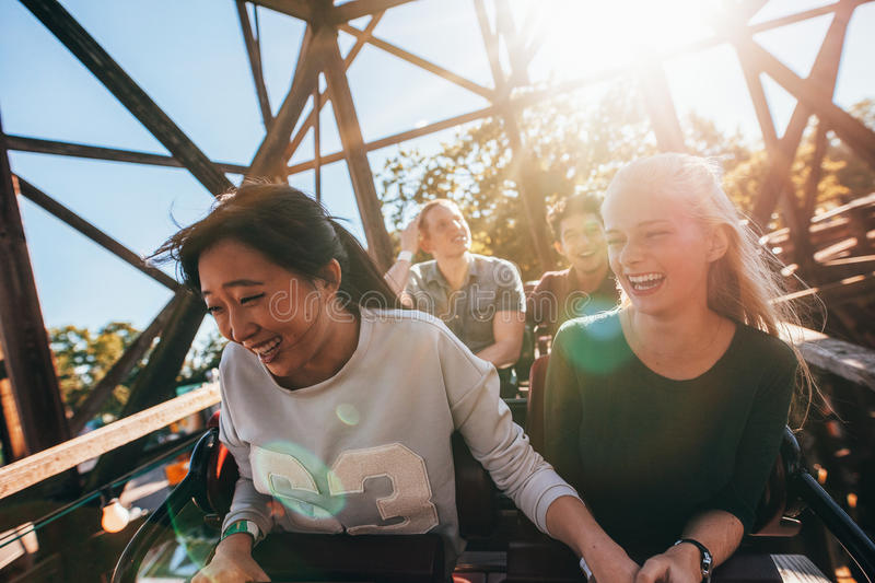 Young people on a thrilling roller coaster ride stock image